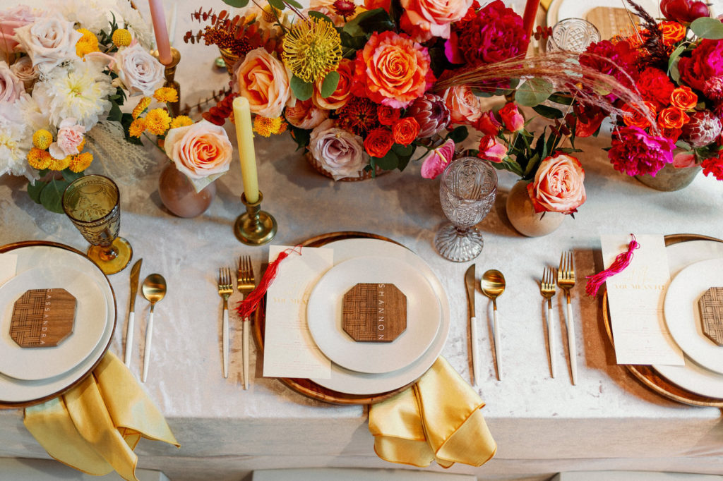 Whimsical and Colorful Wedding Reception Tablescape Decor, Yellow Pincushion Protea, Orange and Blush Pink Roses, Fuschia Pink Flowers, Candlesticks, Wooden Charger, Wood Geometric Shape Place Card, Gold and White Flatware, Yellow Linen Napkin, Vintage Glassware   Tampa Bay Wedding Photographer Dewitt for Love   Linen Wedding Rentals Kate Ryan Event Rentals