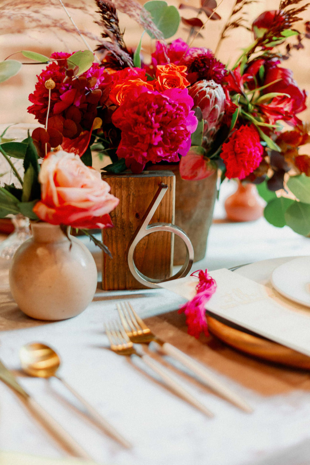 Whimsical and Colorful Wedding Reception Tablescape Decor, Fuschia Pink Flowers, Pink King Protea, Eucalyptus Low Floral Centerpiece, Wooden Table Number, Gold and White Flatware   Tampa Bay Wedding Photographer Dewitt for Love   Wedding Linen Rentals Kate Ryan Event Rentals