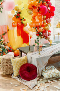 Whimsical and Colorful Wedding Reception Decor, Low Boho Style Picnic Table with Neutral Silk Table Linen, Red, Yellow and Gold Cushions, Woven Basket, Orange, Yellow, Pink, Gold and Fuschia Balloon and Fringe Backdrop, Tall Candlesticks, White Rose Petals | Tampa Bay Wedding Photographer Dewitt for Love | Wedding Linen Rental Kate Ryan Event Rentals