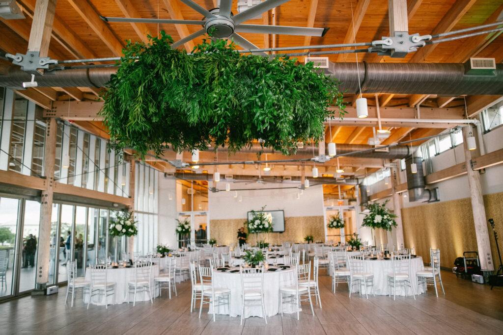 Modern Elegant Wedding Reception Decor, Greenery Hanging Chandelier, Silver Chiavari Chairs, White Linen Round Tables, Tall Floral Centerpieces | Tampa Bay Wedding Rentals Kate Ryan Event Rentals