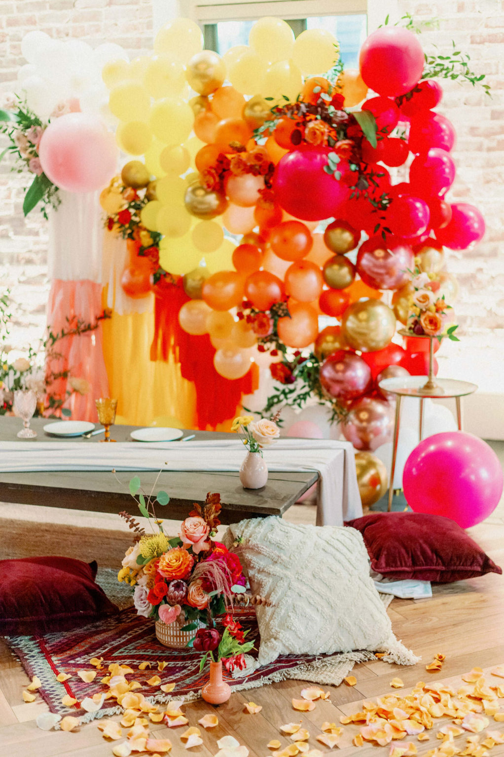 Whimsical and Colorful Wedding Reception Decor, Low Boho Style Picnic Table with Neutral Silk Table Linen, Red, Yellow and Gold Cushions, Woven Basket, Orange, Yellow, Pink, Gold and Fuschia Balloon and Fringe Backdrop, Tall Candlesticks, White Rose Petals   Tampa Bay Wedding Photographer Dewitt for Love   Wedding Linen Rental Kate Ryan Event Rentals   St. Pete Modern Industrial Wedding Venue Red Mesa Events