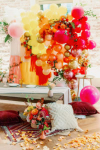 Whimsical and Colorful Wedding Reception Decor, Low Boho Style Picnic Table with Neutral Silk Table Linen, Red, Yellow and Gold Cushions, Woven Basket, Orange, Yellow, Pink, Gold and Fuschia Balloon and Fringe Backdrop, Tall Candlesticks, White Rose Petals | Tampa Bay Wedding Photographer Dewitt for Love | Wedding Linen Rental Kate Ryan Event Rentals | St. Pete Modern Industrial Wedding Venue Red Mesa Events
