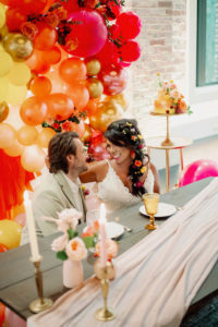 Whimsical Bride with Braided Hair and Flowers and Groom Sitting at Low Picnic Style Table with Neutral Drape Linen, Blush Pink Roses, Tall Candlesticks, Yellow Vintage Glassware, Orange, Yellow, Gold, Pink and Red Balloon Backdrop | Tampa Bay Wedding Photographer Dewitt for Love | Wedding Linen Rentals Kate Ryan Event Rentals | St. Pete Modern Industrial Wedding Venue Red Mesa Events
