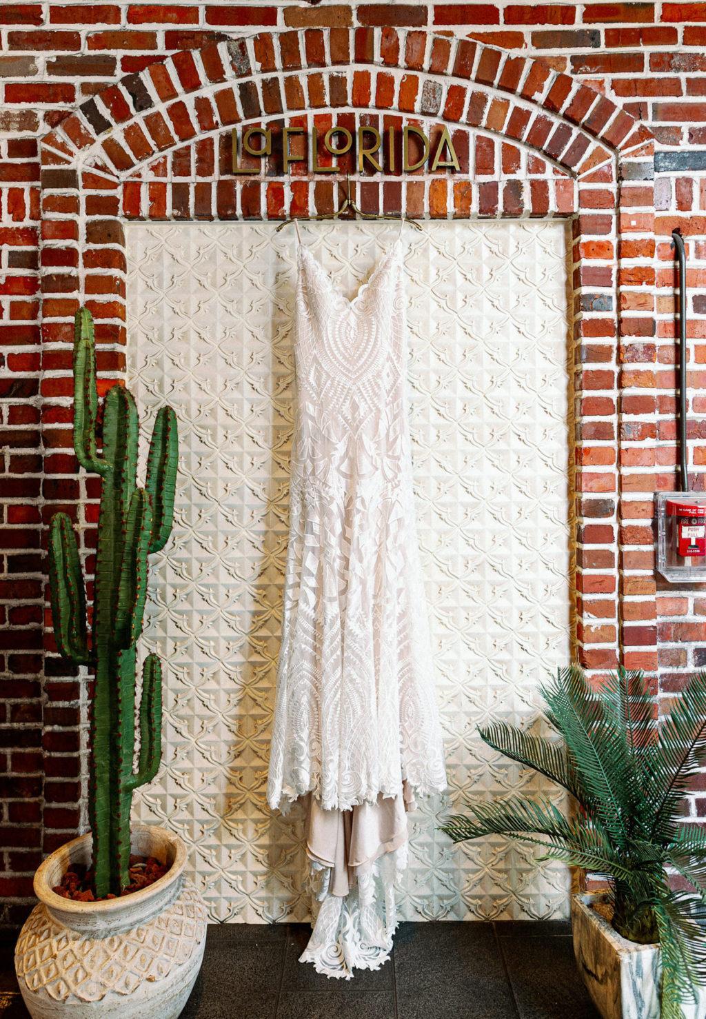 Romantic Boho Lace Spaghetti Strap V Neckline Wedding Dress Hanging on Red Brick Wall   Tampa Bay Wedding Photographer Dewitt for Love