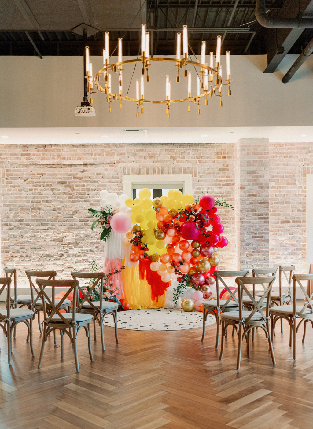 Colorful Whimsical Wedding Ceremony Decor, Wooden Cross Back Chairs, Yellow, Orange, Pink, Gold Balloon Fringe Ceremony Backdrop | Downtown St Pete Modern Industrial Chic Wedding Venue Red Mesa Events | Tampa Bay Wedding Photographer Dewitt for Love | Wedding Chair Rentals Kate Ryan Event Rentals