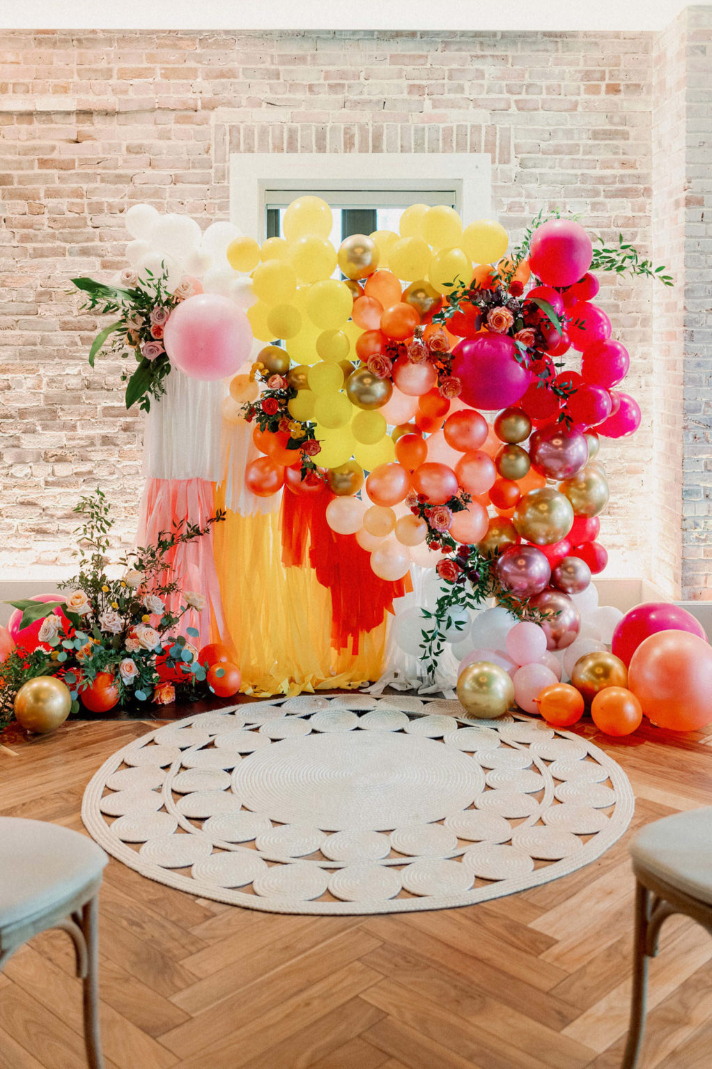 Colorful Whimsical Wedding Ceremony Decor, Wooden Cross Back Chairs, Yellow, Orange, Pink, Gold Balloon Fringe Ceremony BackdropDowntown St Pete Modern Industrial Chic Wedding Venue Red Mesa Events   Tampa Bay Wedding Photographer Dewitt for Love