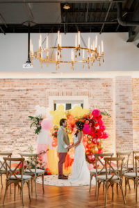 Bride and Groom Exchanging Wedding Vows, Whimsical and Colorful Wedding Decor, Yellow, Pink, Orange, White, Gold Fringe and Balloon Ceremony Backdrop, Wooden Cross Back Chairs, Gold and Candlestick Chandelier, White Brick Wall | Tampa Bay Wedding Photographer Dewitt for Love | St. Pete Modern Industrial Wedding Venue Red Mesa Events | Wedding Chair Rentals Kate Ryan Event Rentals