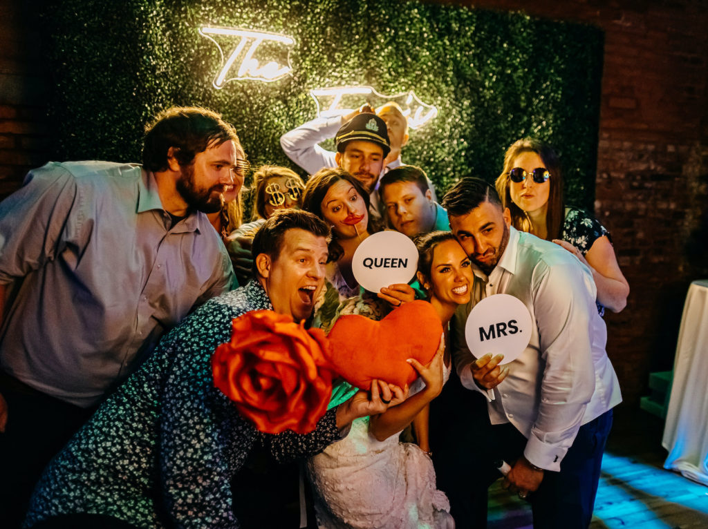 Open Air Photo Booth with Greenery Backdrop Wall and Neon Sign | Tampa Bay Luxury Rental Gala Photo Booth